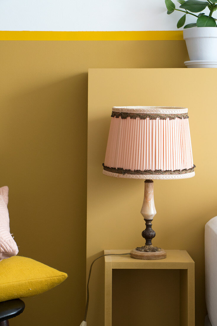 Old table lamp on bedside table against ochre wall with ledge