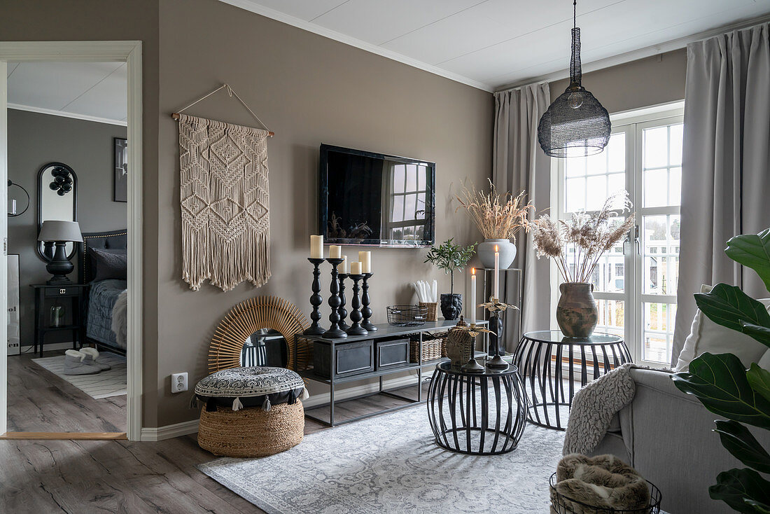 Candlesticks on a lowboard, a television and macrame on a taupe wall in a living room