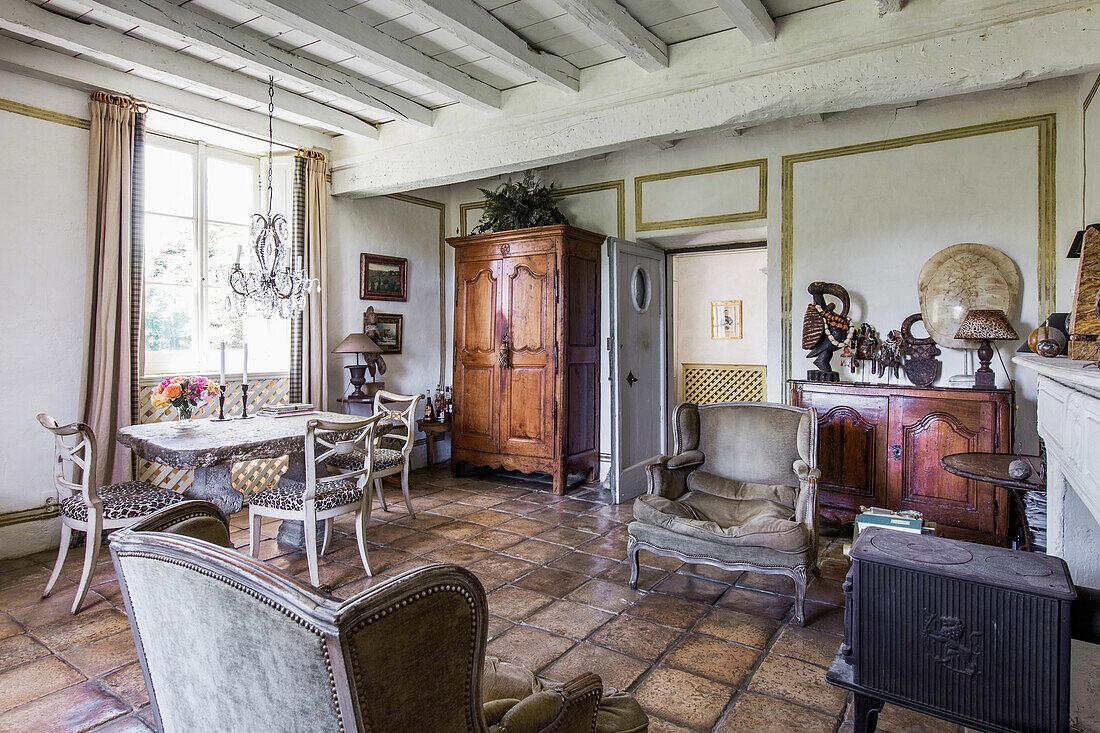 Antike Sessel und Holzschränke und Steintisch mit Stühlen im Wohnraum mit Fliesenboden