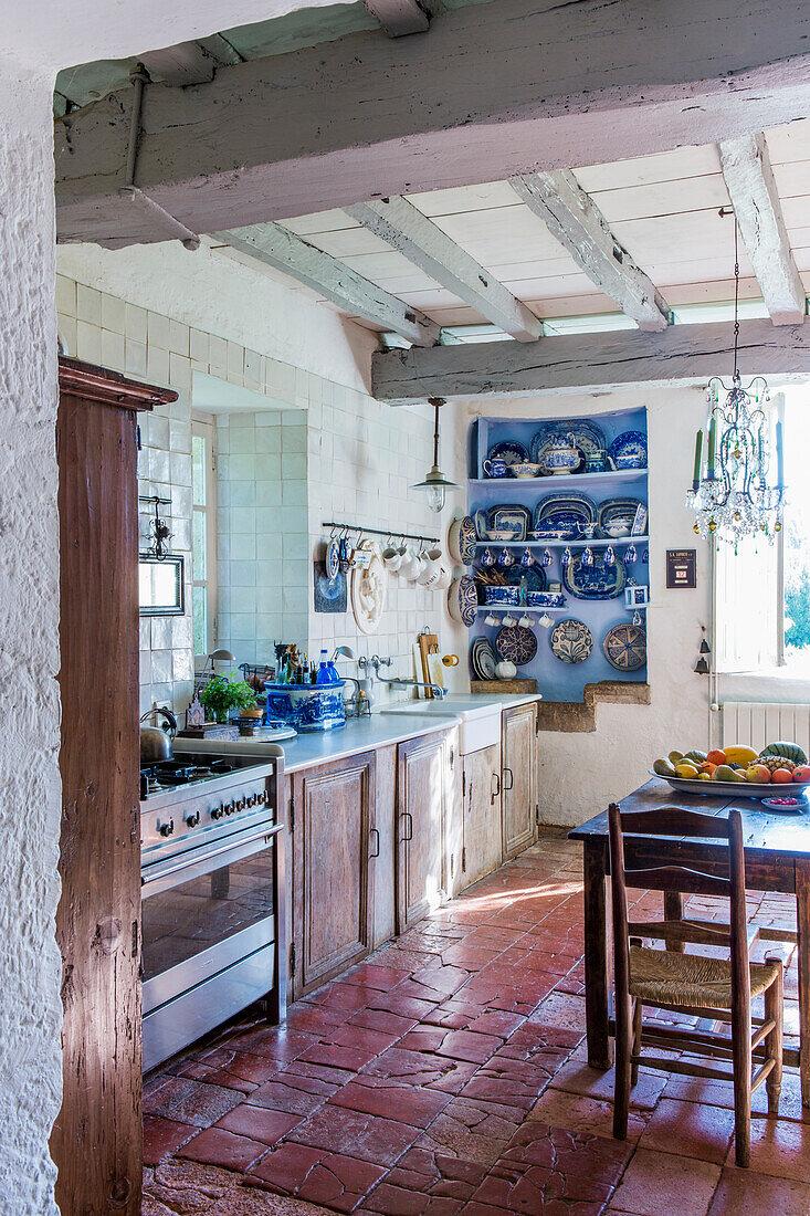 Rustikale Küche mit Holzbalken und Terrakotta-Fliesenboden