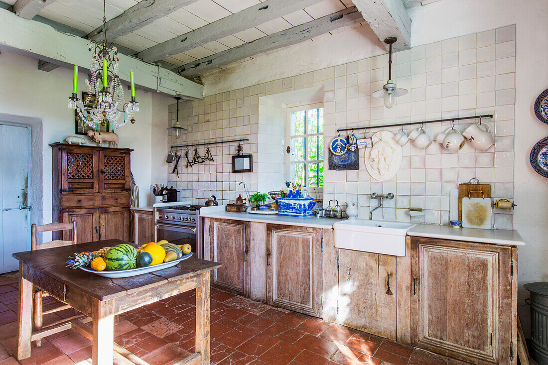 Wooden table in rustic kitchen with wooden beams and terracotta tiled floor