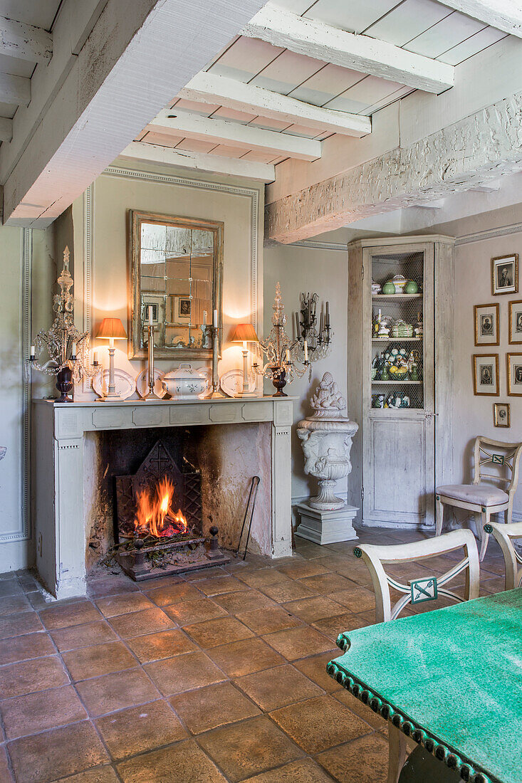 Fireplace with fire in dining room with beamed ceiling