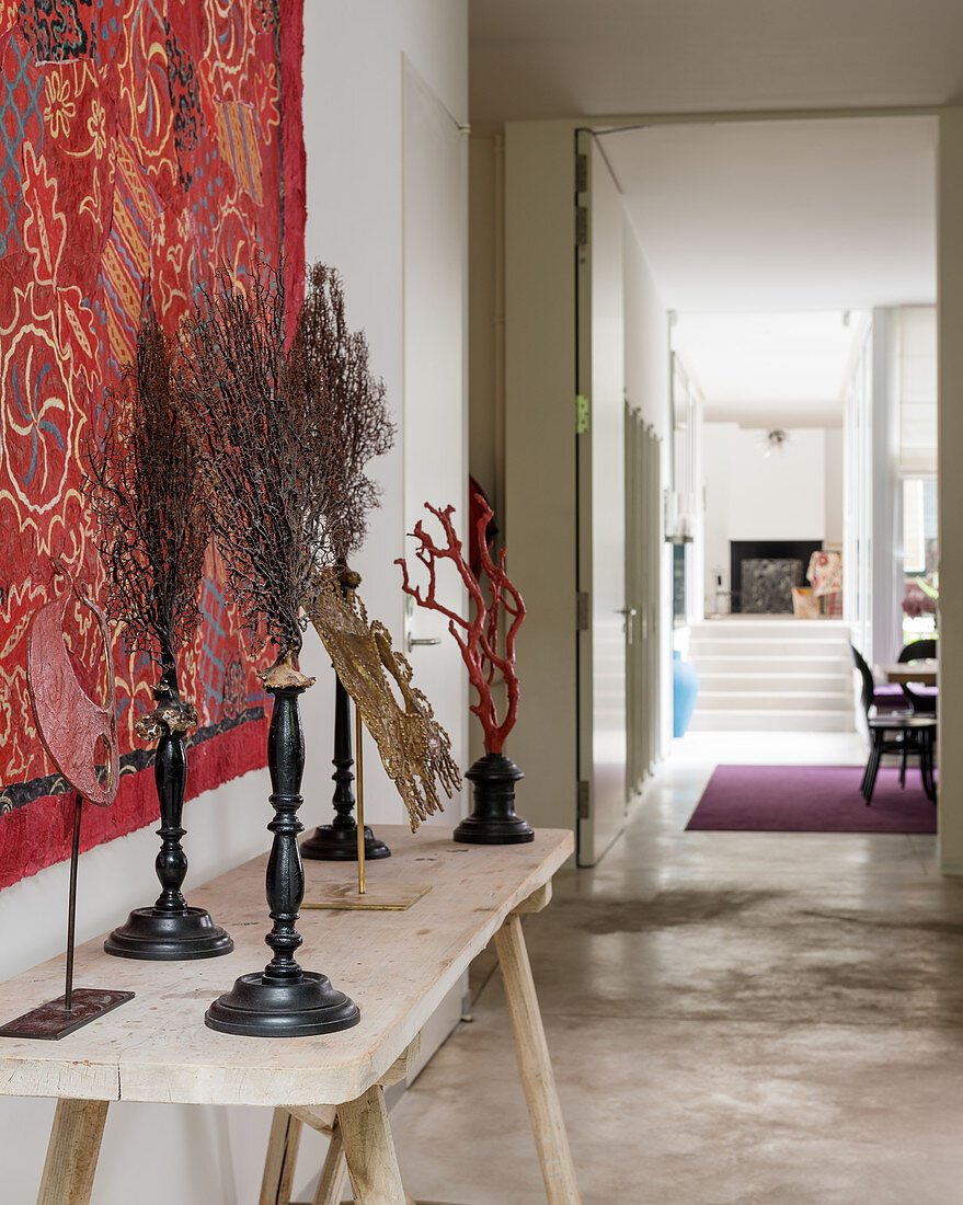 Artwork displayed with red wall covering in atelier hallway