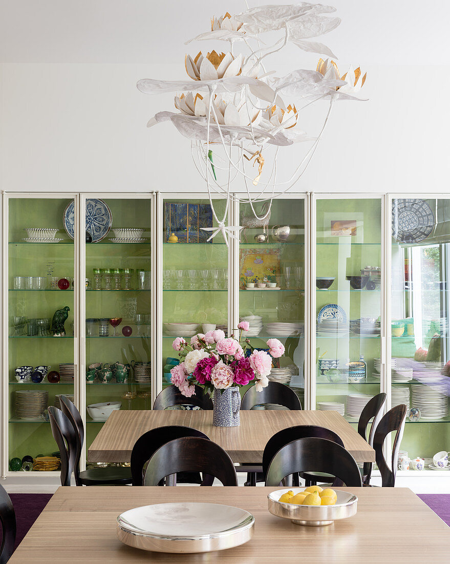 Glass fronted cabinet with pair of oak topped tables and vintage chairs allow 16 to be seated for dinner