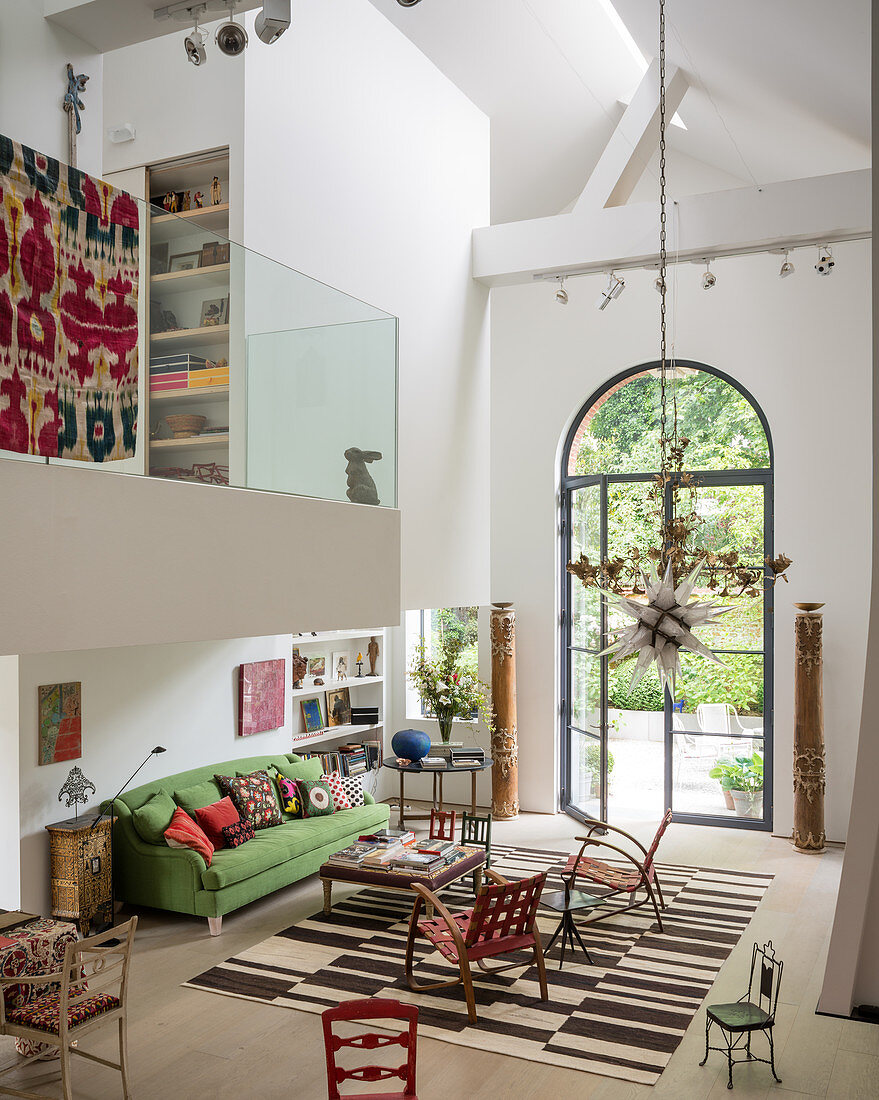 Triple-height living space with mezzanine and old textiles adding colour