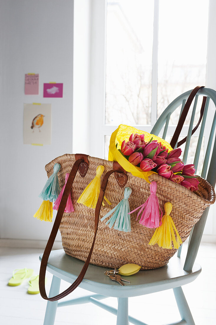 Raffia shopping basket decorated with paper tassels