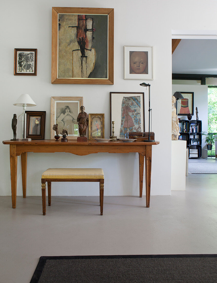 Stool at console table covered with pictures and sculptures in artist's house