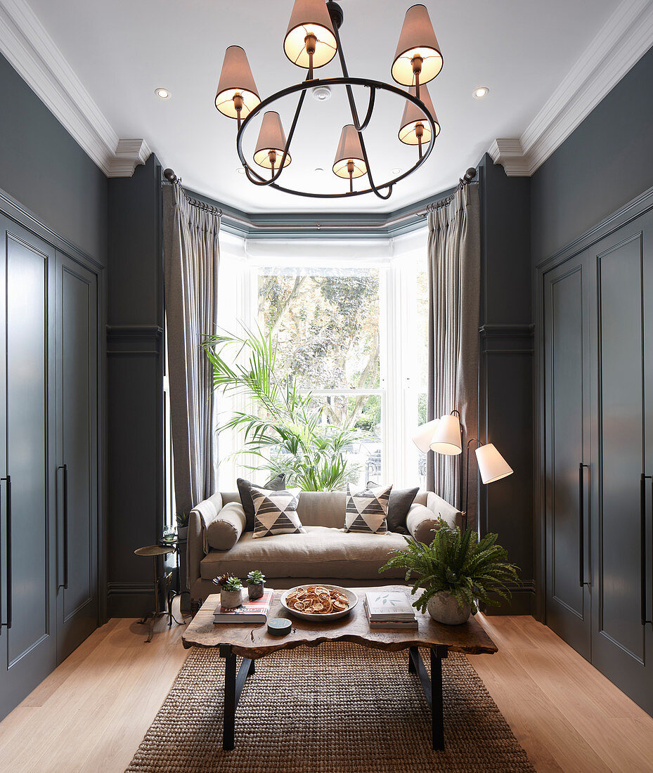 Small living room with grey fitted cupboards and sofa in bay window