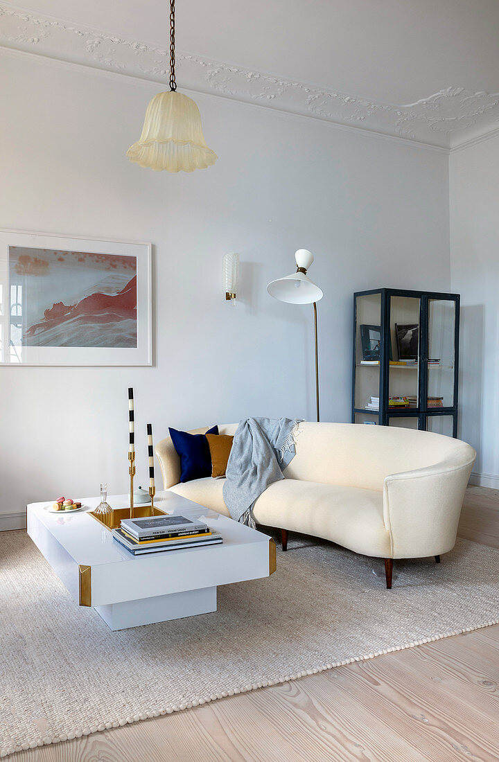Curved sofa and white coffee table in living room