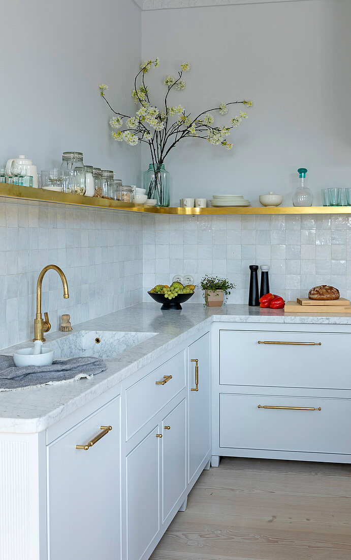 Marble, glazed tiles and golden accents in white kitchen