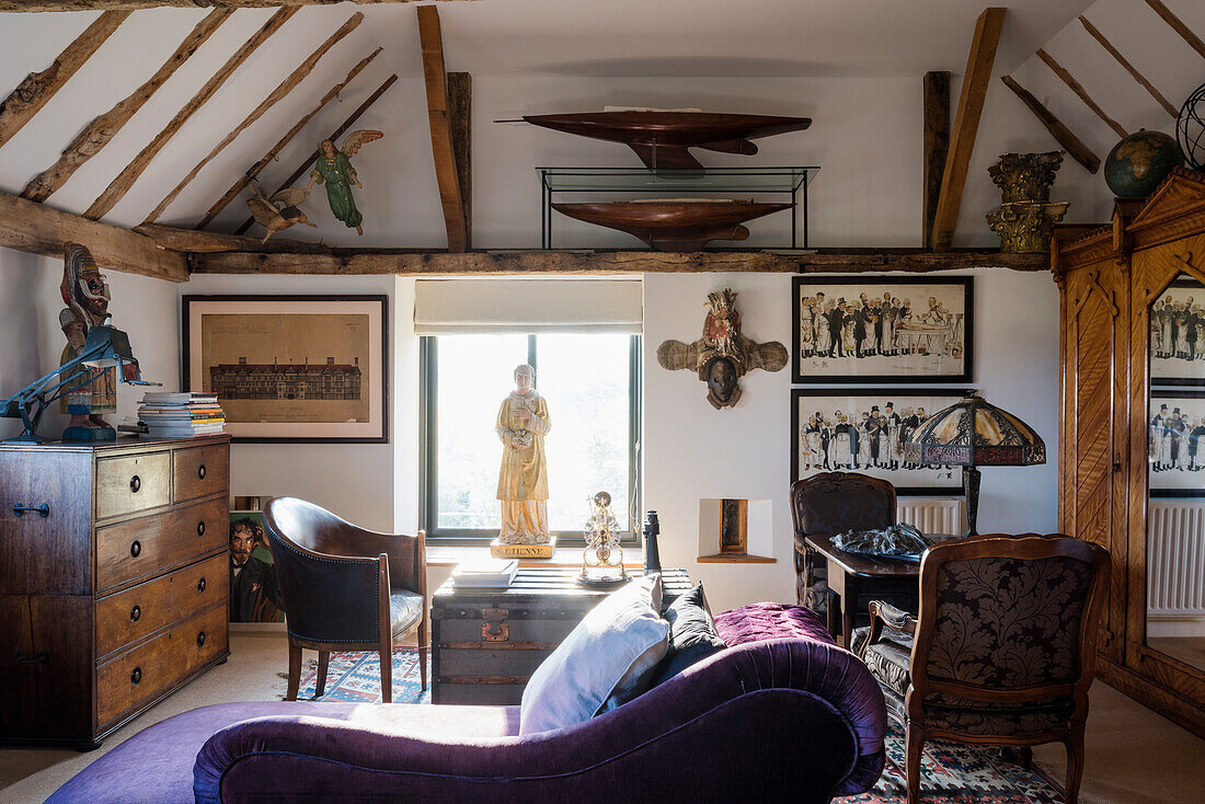 Purple chaise longue with statue in window and writing table lit by an 60's lamp