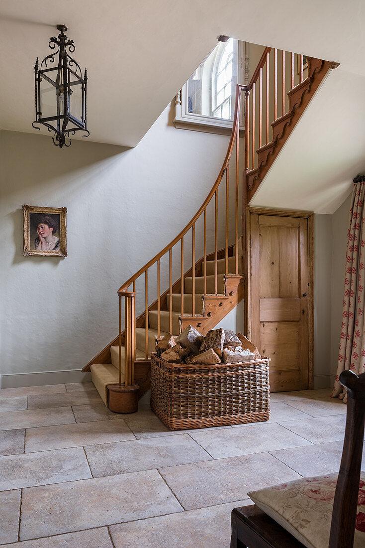 Log basket in spacious entrance hallway of restored farmhouse