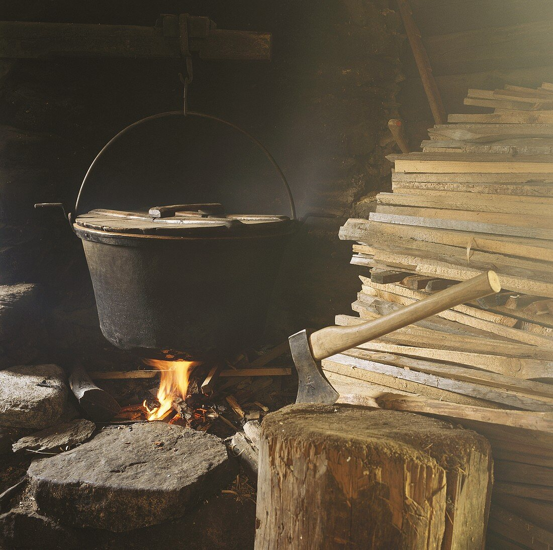 Cooking pot on open fire, axe and wood in old shack
