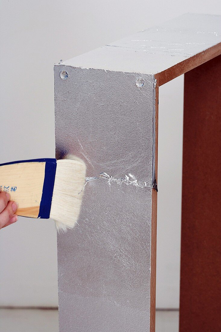 Making a wall table (smoothing down stuck-on silver foil with a brush)