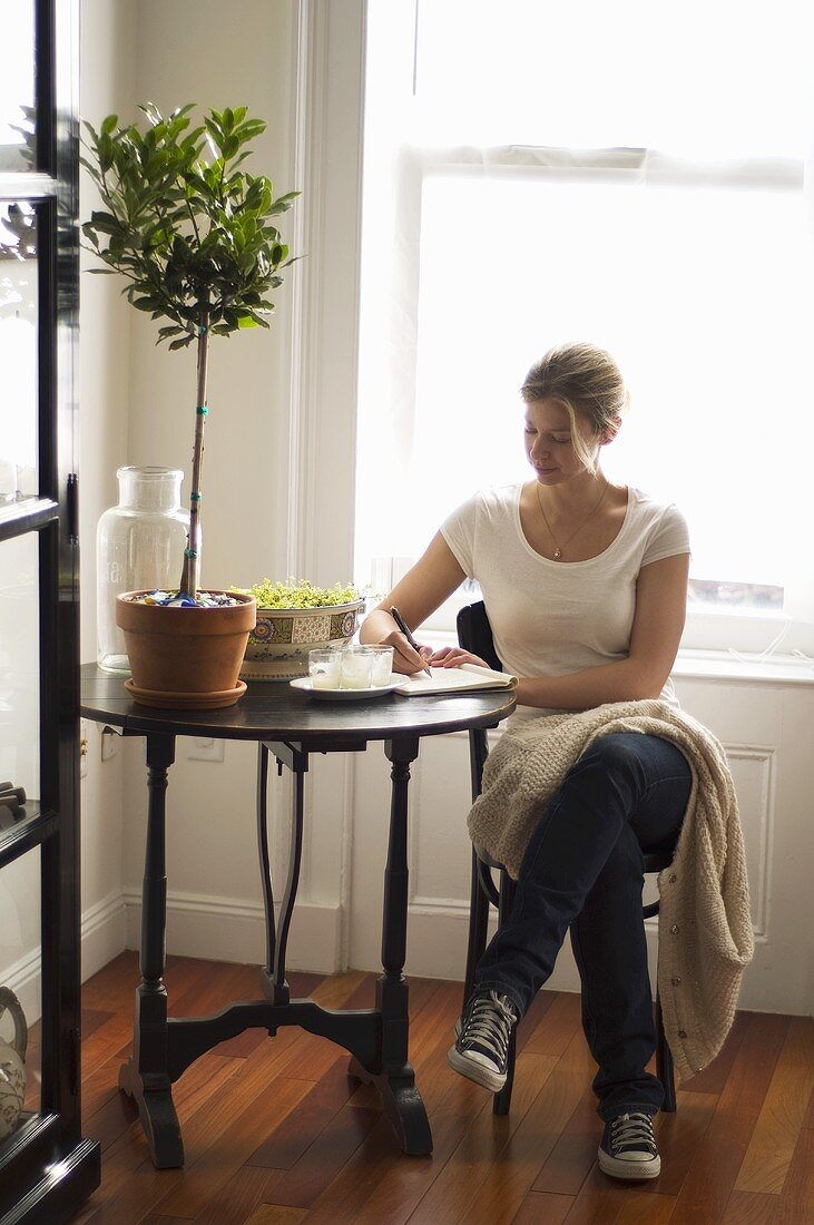 Woman writing at antique French-style bistro table