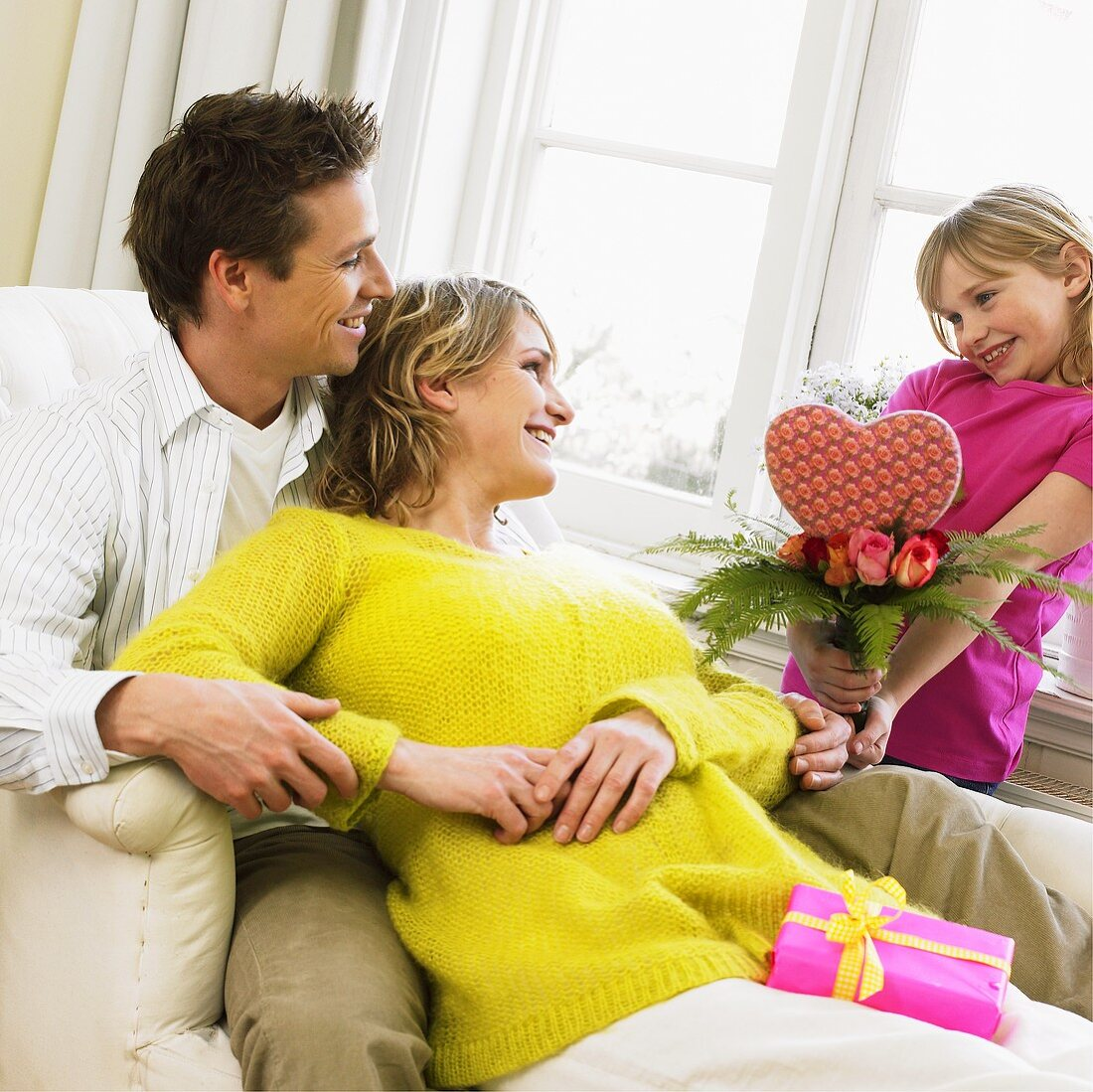 Girl giving her parents a bouquet with a heart