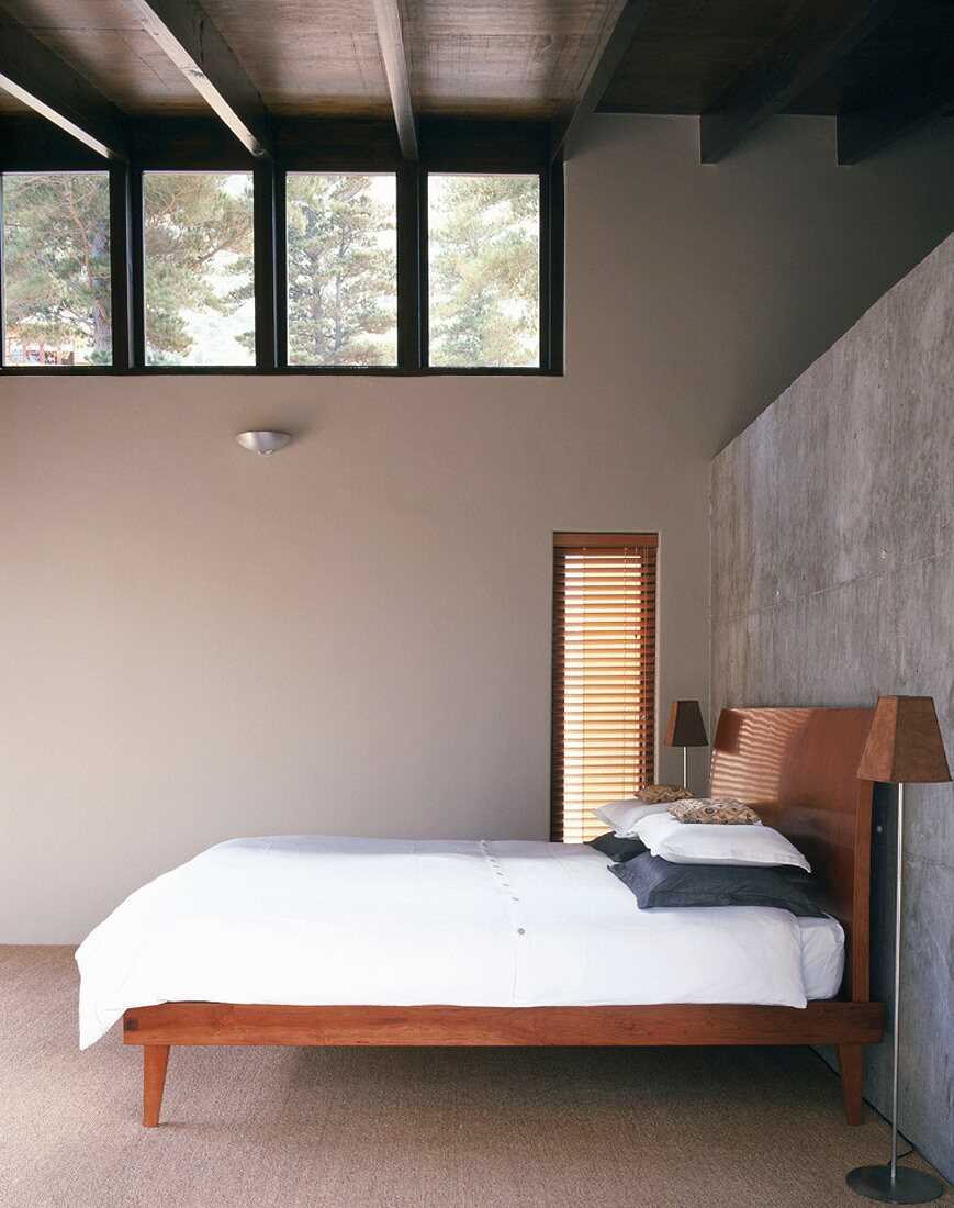 Purist bedroom with double bed and standard lamp against half-height exposed concrete wall