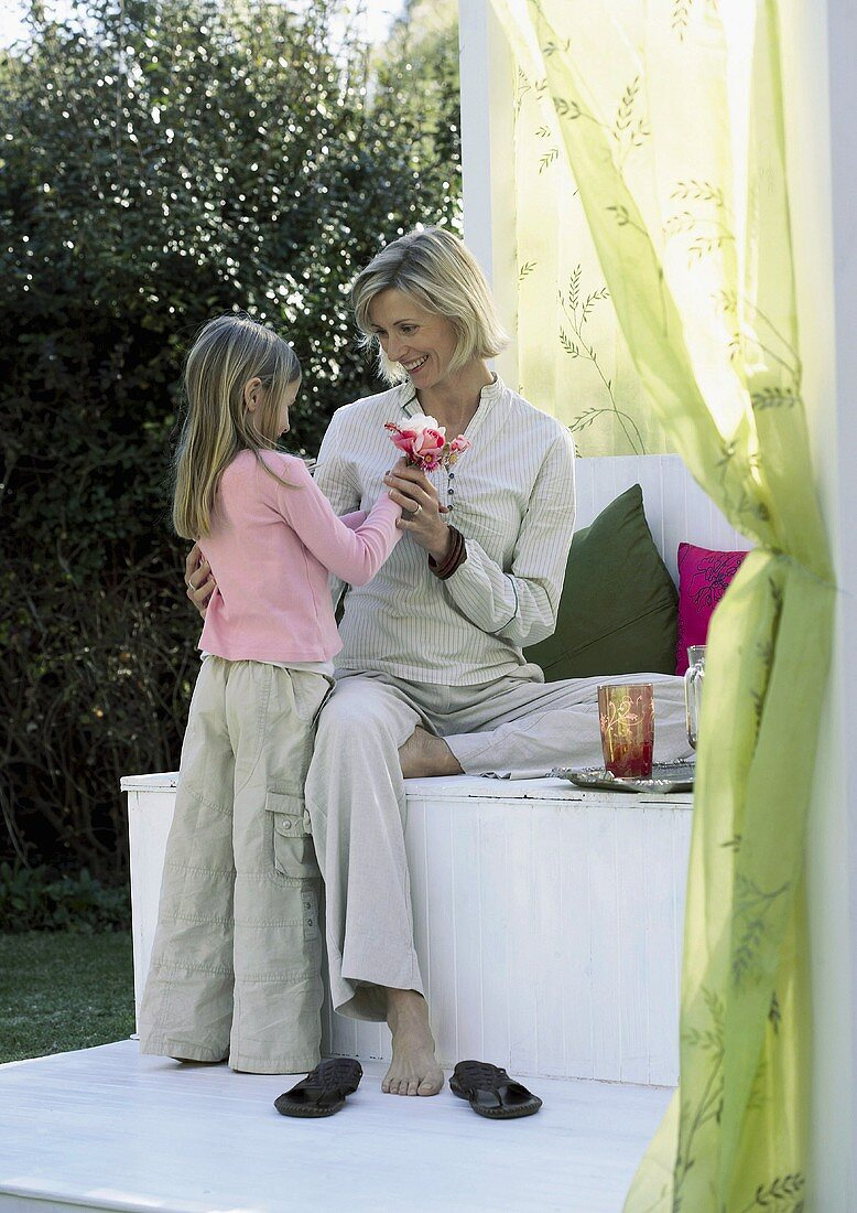 Daughter giving her mother a small posy of flowers in garden