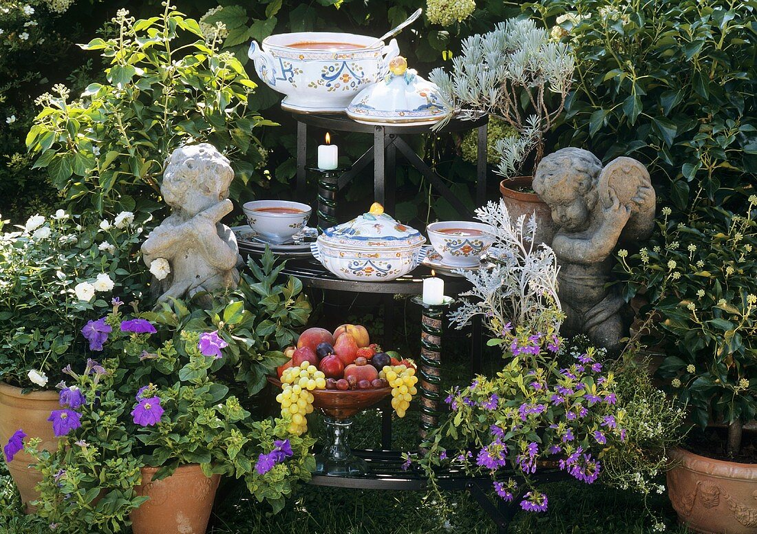 Tomato soup, bowl of fruit on tiered stand in garden