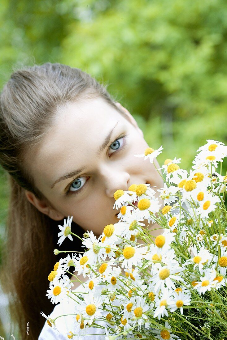 Young woman with a bunch of fresh chamomile