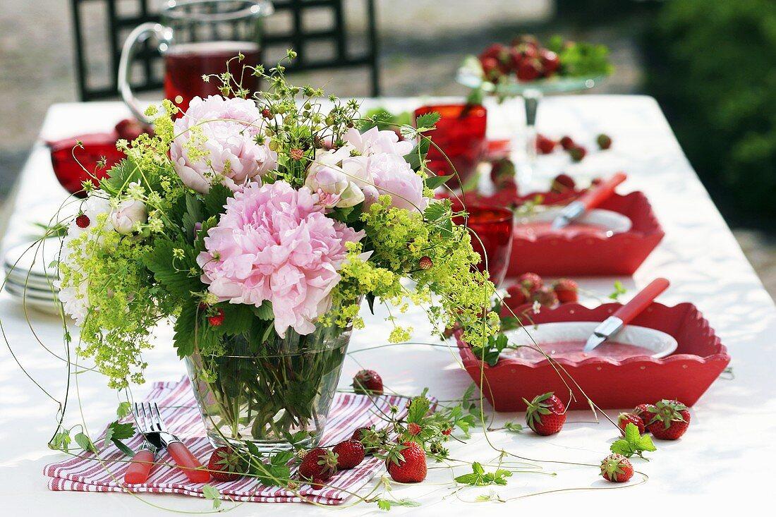Vase of peonies, wild strawberries and lady's mantle