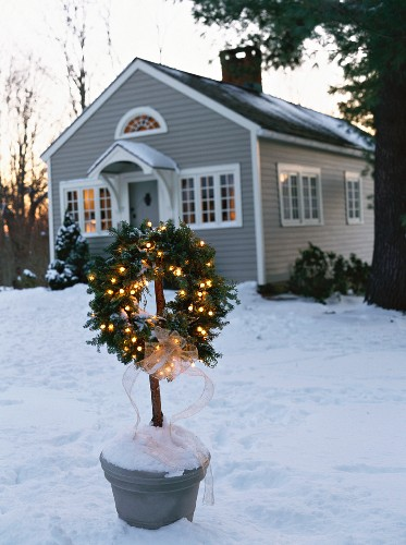 Fir wreath with lights outside a house in the country (USA)