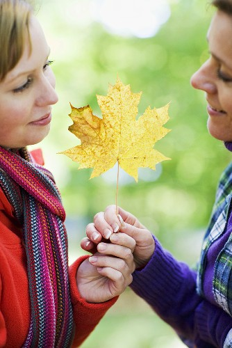 Mother and daughter holding an autumn leaf