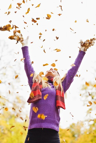 Woman throwing autumn leaves in the air