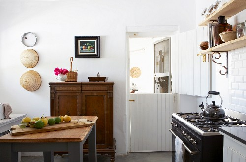 Bright, vintage-style kitchen with retro gas cooker and simple wooden shelving on white-tiled wall