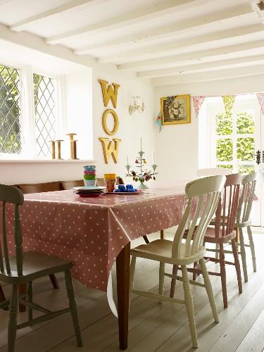 Esszimmer mit gepunktetem Tischtuch und antiken selbstbemalten Holzstühlen