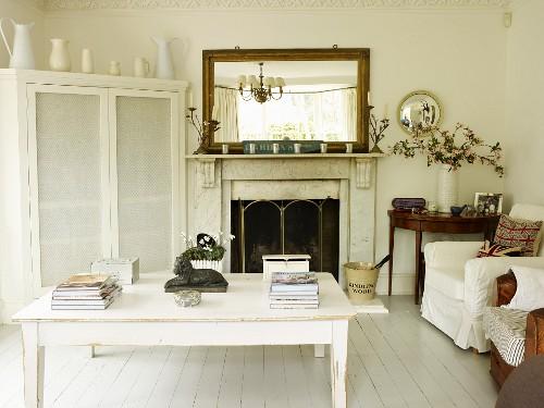 Wohnzimmer mit offenem Kamin, Wandspiegel, weiss lackiertem Tisch, Polsterstühlen, Eckschrank und antikem Beistelltisch