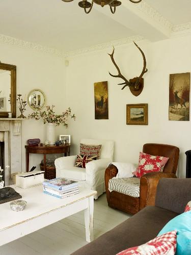 Polsterstühle mit Dekokissen, weiss lackierter Holztisch, Sofa und Wandbilder mit Jagdmotiven und Hirschgeweih im Wohnzimmer