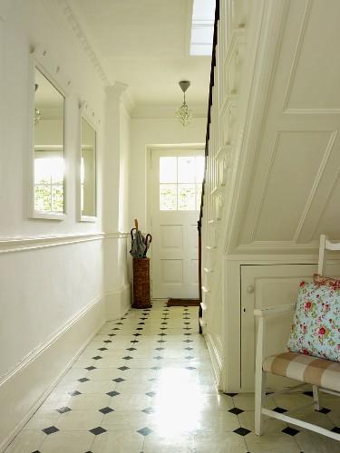 Flur mit Fliesenboden, weiss lackierter Holztreppe, weissen Wänden und Wandspiegeln