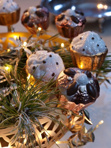 Metal, cake-shaped decorations on brass tray with fairy lights