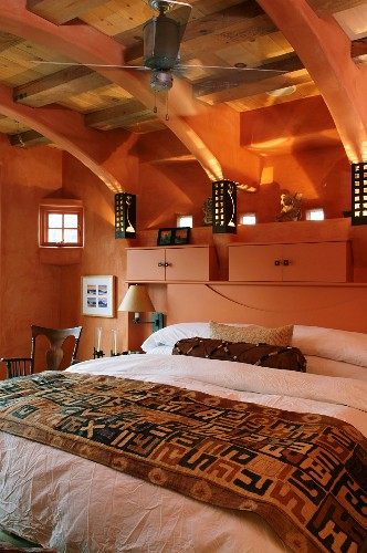 Attic bedroom with exposed wooden roof structure - double bed against salmon pink wall with small cupboards on headboard in same colour