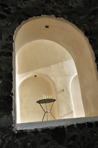 View of modern metal table in austere vaulted interior with niches seen through arched window