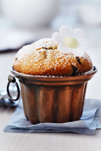 Muffin in copper cake mould decorated with edible paper flower