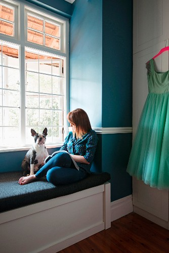 Woman and dog on upholstered window seat against blue-painted wall