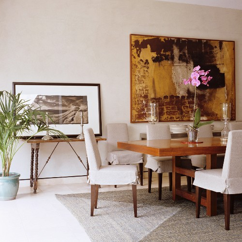 Loose-covered chairs at long table in exotic wood and modern artwork on wall in classic, elegant dining room