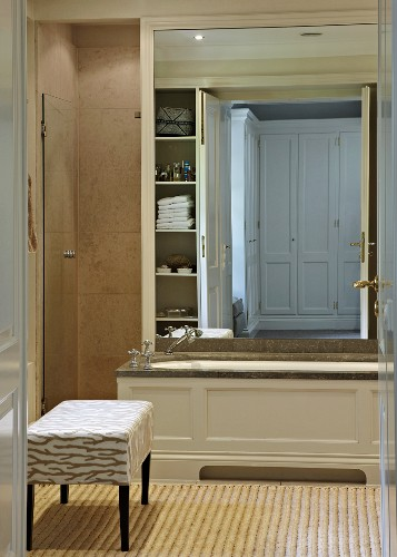 View through and open door of a paneled bathtub in front of a large wall mirror and upholostered stool on a bamboo runner in country home style