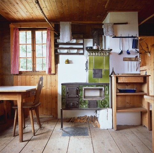 Rustic kitchen-utility room with tiled stove and broad, rough floorboards