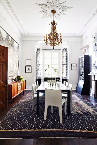 Black table and white chairs below chandelier and stucco elements on ceiling in eclectic dining room