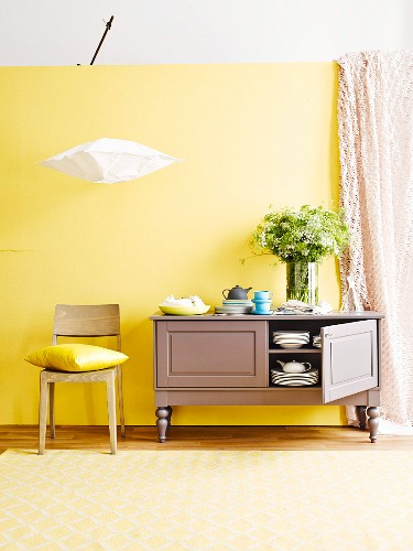 Crockery in small, country-house sideboard, modern wooden chair and Japanese rice paper lamp against yellow wall