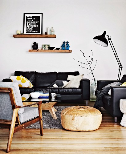 Pouffe between fifties-style armchair and leather sofa set and black, metal standard lamp in living room