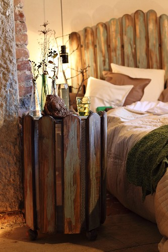 Side table made of recycled wooden slats and double bed with headboard made from picket fence