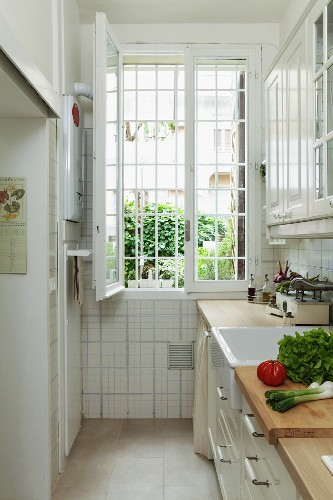 Vegetables on kitchen counter in narrow kitchen with open, barred window at far end