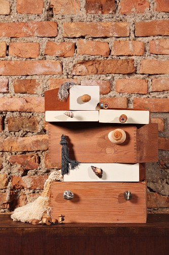 Stacked boxes with furniture handles attached to fronts against rustic brick wall