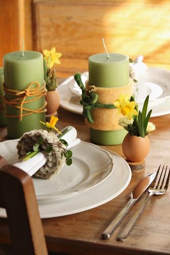 Grüne Kerzen mit Dekobändern umwickelt und Gedecke mit österlichem Schmuck auf Tisch