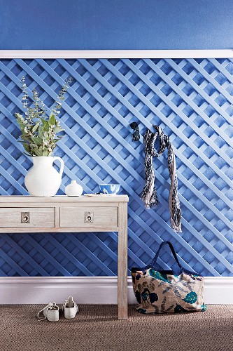 Wooden trellis painted pale blue and used as a coat rack behind ornaments on console table with drawers