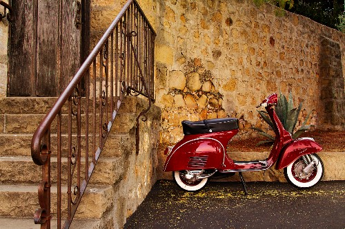 Red Vespa Scooter Parked by a Stone Wall